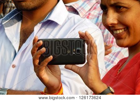 HYDERABAD,INDIA-MARCH 27:Indian young adult woman shoot an event with mobile phone on March 27,2016 in Hyderabad,India.