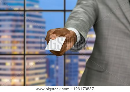 Afro businessman gives visit card. Blank card on megalopolis background. Realtor in capital city. Place for your advertising.