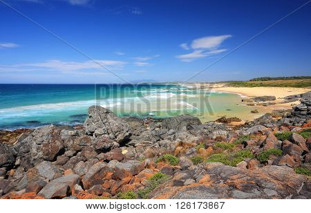 Beautiful sunny day Bingie Beach views along the beach for 4.3km the area is known for its colourful orange black and grey rocks known as magma igneous intrusive rocks. They look spectacular against the sapphire blue seas