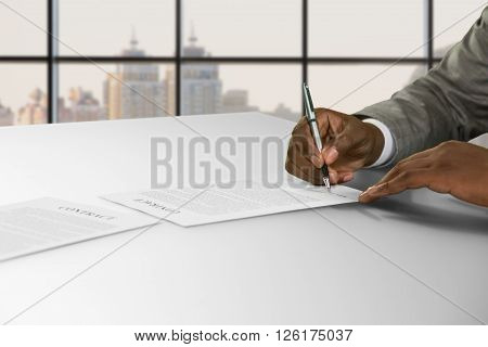 Afro businessman's hand signs contract. Man signing contract in town. He agreed to the proposition. Good salary and nice perspective.