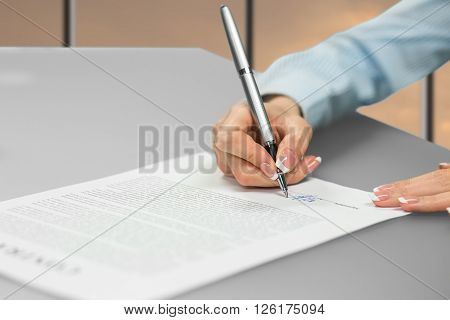 Young lady's hand signing document. Businesswoman writing at the table. Putting signature with gray pen. Choice of career.