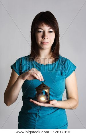 Young Woman In Blue Shirt Holding Candlestick With Burning Candle, Looking At Camera