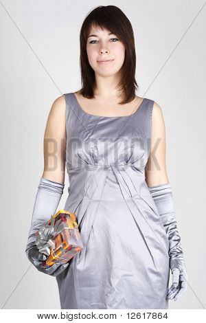 Beauty Brunette Woman In Silver Evening Dress And Gloves Holding Gift, Smiling And Looking At Camera