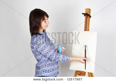 Young Girl In Blue Shirt Standing Near Easel And Painting, Blank Canvas