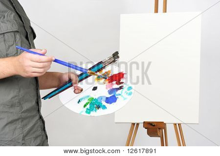 Closeup Of Man Holding Brushes And Palette, Blank Canvas On Easel