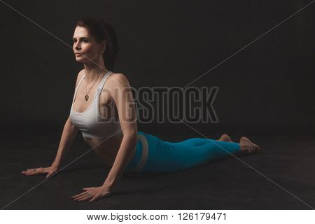 Beautiful sporty yogi girl practices yoga asana over black background