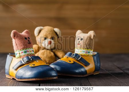 Baby Boots And Toy Doll On Wooden Table