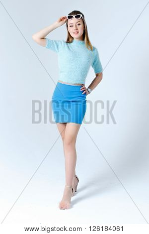 Beauty sexy fashion model girl wearing retro blue clothes with white sunglasses posing in studio, isolated on gray background. Beautiful Lady face.