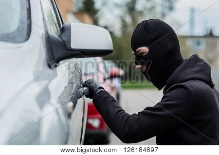 Car Thief Pulls The Handle Of A Car.