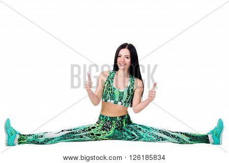 flexible young slender woman sit on twine and stretching showing fingers up sign OK. Isolated on white background