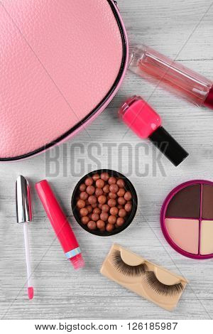 Makeup set with beautician, false eyelashes and cosmetics on white wooden background