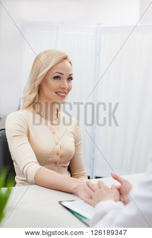 I rely on you. Beautiful young woman is visiting the doctor. She is holding the hand of gynecologist and looking at her with trust. The lady is smiling