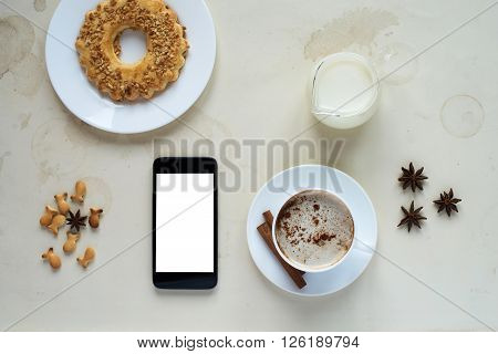Breakfast with a a cup of coffee, milk, a cookie and a smartphone.