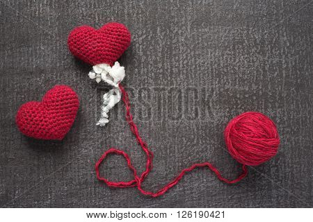 Crocheted red hearts on a grunge board with a ball of woolen yarn. One heart is not finished.