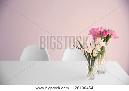 Beautiful tulips and irises on dinning table against white wall background