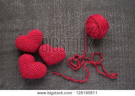 Crocheted red hearts on a grunge board with a ball of woolen yarn.
