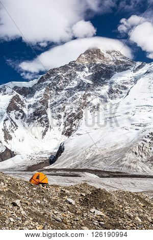 Glacier Moraine with Orange Camping Tent and High Altitude Snowbound Mountain Peak with Cloudy Sky