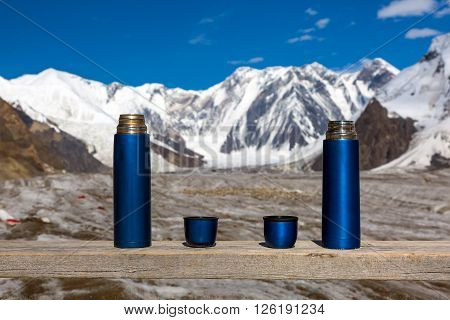 Two Blue Thermoses and Cups on Wooden Table with Beautiful Himalaya Mountains and Clear Blue Sky on Background Active Lifestyle Concept