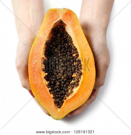 Female hands holding a halved papaya on white background