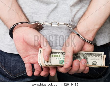 Handcuffs On Hands Holding Money