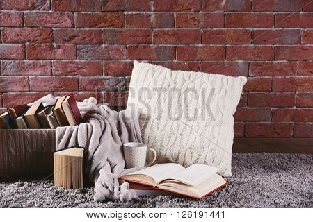 Pile of books in box on brick wall background