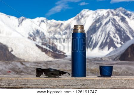 Blue Travel Thermos with Opened Cup and Sunglasses on Wooden Table High Majestic Himalaya Mountain Range with Snow and Ice on Background