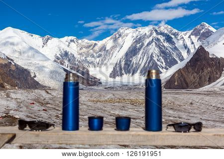 Active Lifestyle Couple Concept Two Blue Travel Thermoses Cups and Sunglasses on Wood Table and Mountain Landscape Focus on Mountains Thermoses are Blurred
