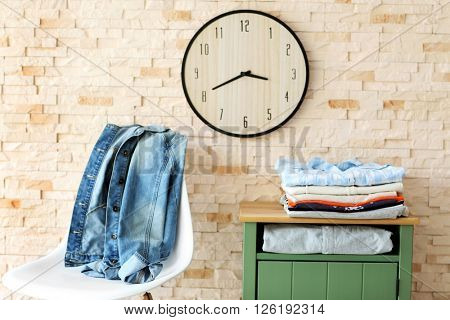 Male clothes lying on bedside table in front of brick wall background