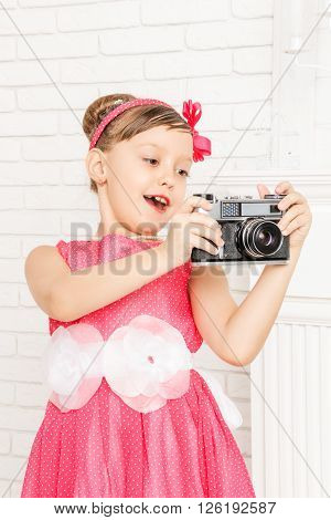 little girl looks at retro camera and wonders