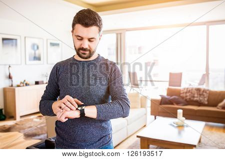 Casual hipster man working from home using smart watch, standing in living room