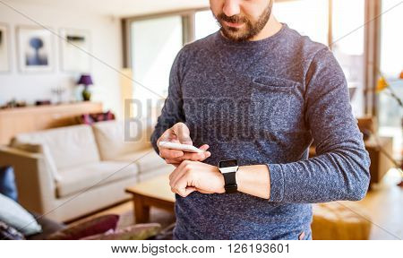Unrecognizable casual man working from home using smart phone and smart watch, standing in living room