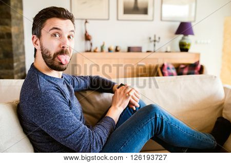Man at home sitting on sofa using smart watch, making funny face, sticking tongue out