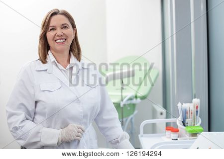 Professional gynecologist is preparing for checkup. She is standing in her office and smiling. The woman is looking at camera happily