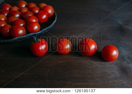 ripe tomatoes, cherry tomatoes on a wooden table, cherry tomatoes on a ceramic plate