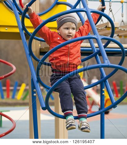 Happy little boy climbing on children playground, spring outdoors