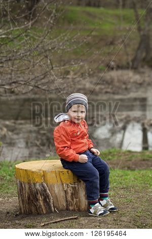 Little boy sitting on a stump in the spring park. Baby boy in orange jacket, outdoors