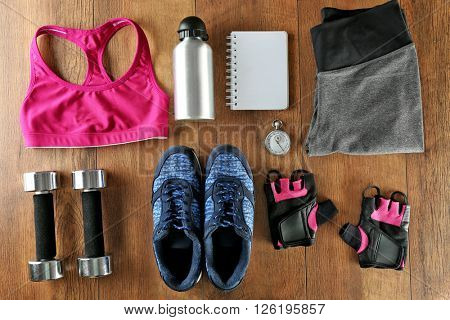 Athlete's set with female clothing, equipment, bottle of water and notebook on wooden background