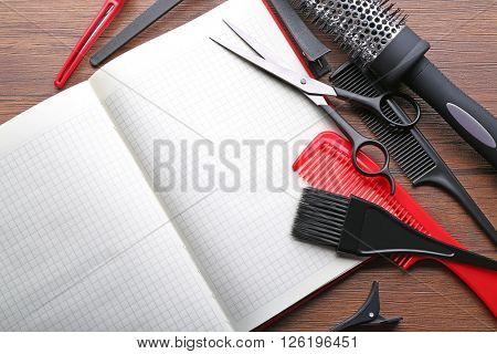 Professional hairdressing equipment on wooden table, copy space
