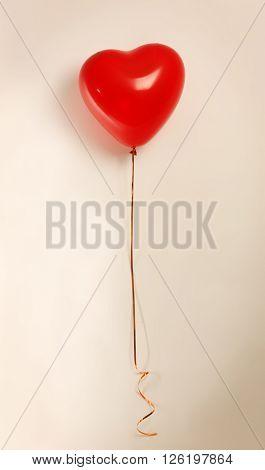 Red heart balloon on light background