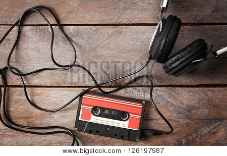 Retro cassette with headphones on wooden table, closeup