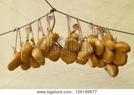 Amsterdam, Holland, April 9, 2016, Smoked scamorza cheeses hanging on ropes on the Noorder market