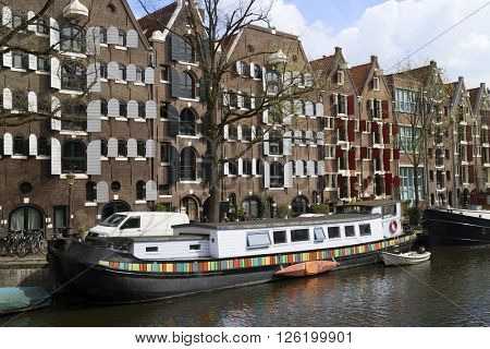 Amsterdam, Holland, April 9, 2016, Colorful Houseboat in a canal in springtime with restored warehouses in the background