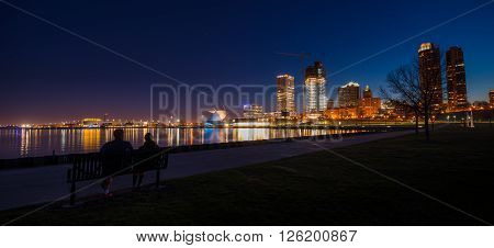 Couple sitting on a bench looking at City of Milwaukee Wisconsin at Night