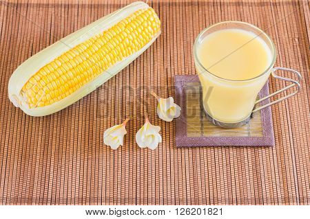 Corn milk in glass kernel corn in bowl and fresh corn
