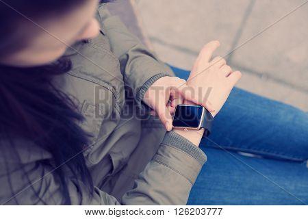 Hands Of A Girl Using Her Smart Watch Outdoors