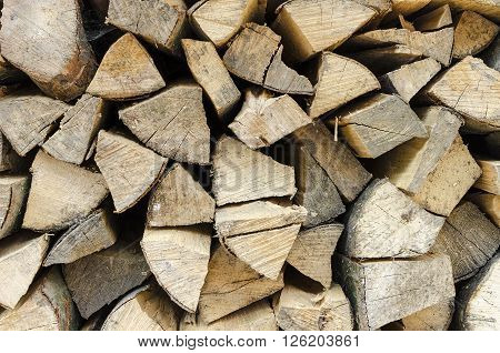 Background of stacked conducting firewood chopped. Close-up.