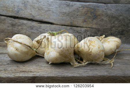 jicama on grunge wooden background, whole, tuber, white, yellow
