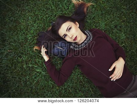 Young Girl Lying On Green Grass In Park