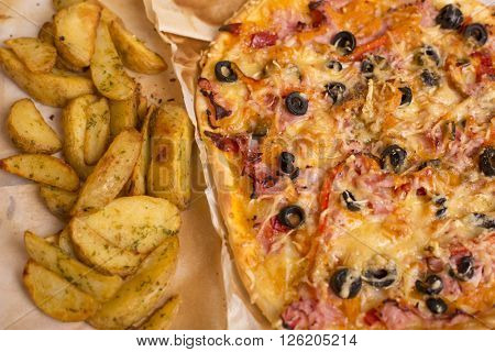 Homemade pizza with french fries on a wooden table