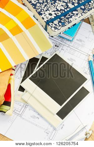Interior designer's working desktop, an architectural plan of the house,  color palette and fabric samples in yellow shades, copy space on instant empty photos